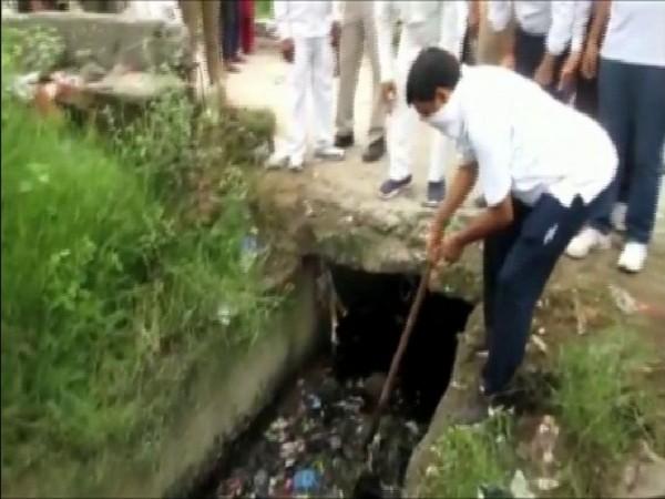 Rampur DM Anjaneya Kumar Singh engaged in cleaning a drain in Rampur on Saturday morning. Photo/ANI