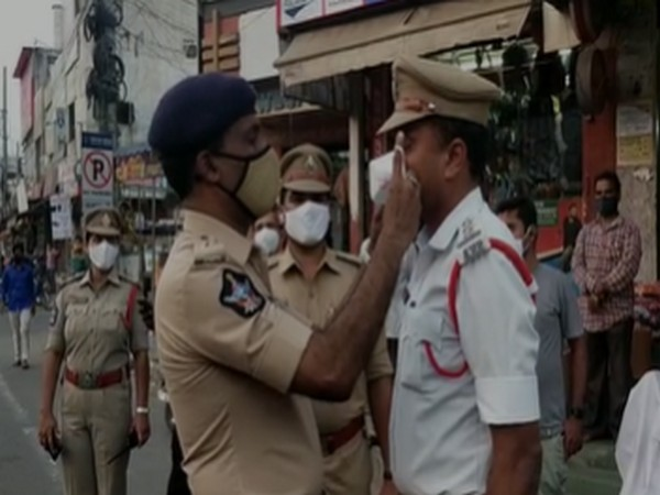 Guntur SP Ammi Reddy making Circle Officer Mallikarjuna Rao wear a mask. [Photo/ANI]