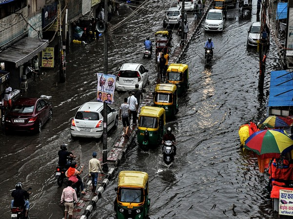 Vehicles wade through a flooded street after heavy rainfall in New Delhi on Sunday. (ANI Photo)