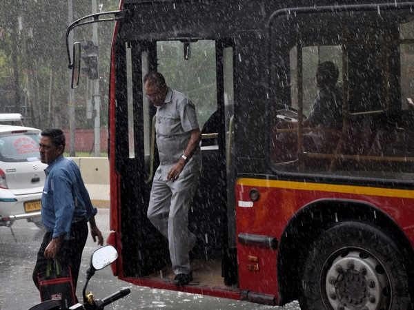 People step out from a bus as it rains in New Delhi on Monday. (ANI Photo)