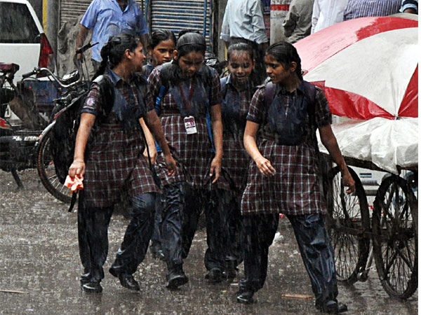 A group of schoolgirls walk during heavy rainfall in Old Delhi. (ANI Photo)
