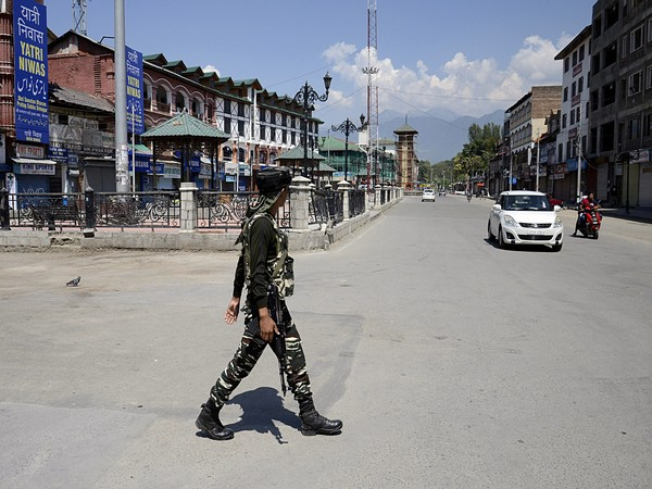 A security person crosses road as a vehicle comes towards him in Kashmir. File photo/ANI