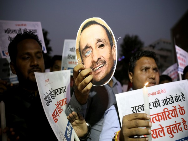 Protester holds up picture of expelled BJP legislator Kuldeep Singh Sengar (File photo)