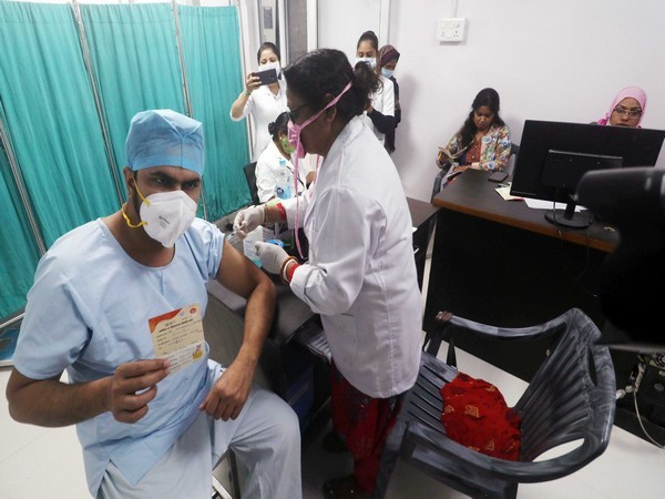A beneficiary shows his report card as he gets COVID-19 vaccine at Eraz Medical College and Hospital, in Lucknow on Saturday.