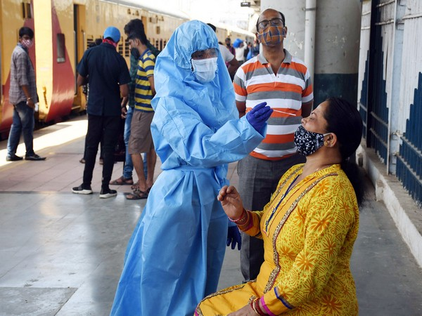 BMC health worker collects a nasal sample from a passenger for Covid Antigen test at Dadar station, in Dadar on Sunday. (Photo/ANI))