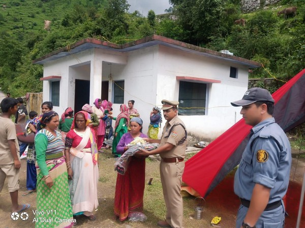 Police distributed relief material in Chamoli on Wednesday. Photo/ANI