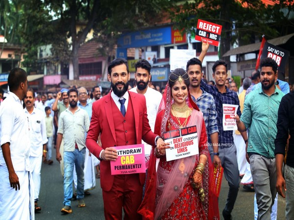 Newly-married couple holding Anti-CAA, NRC placards to mark their protest in Kerala. Photo/ANI