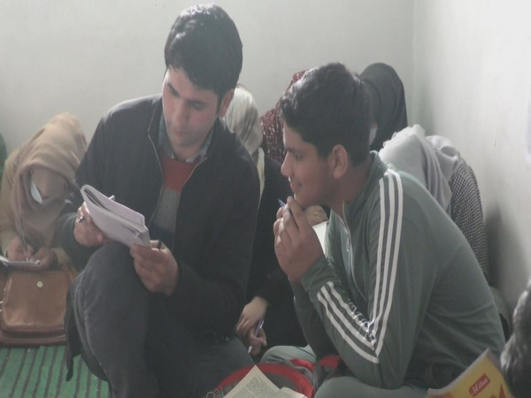 Malik Mukhtar teaching calligraphy to a student at his institute in Baramulla.