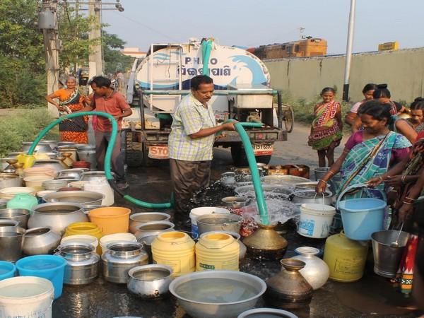 People seen filling water into buckets in Odisha's  Sambalpur. (Photo/ANI)
