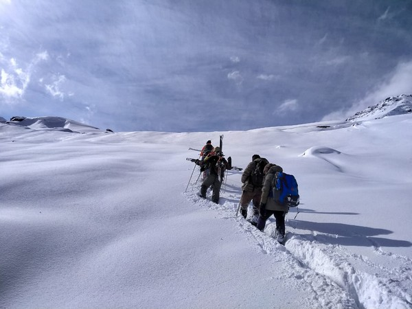Two people crossing Rohtang pass with the help of rescue team deployed at Koksar on Tuesday. Photo/ANI