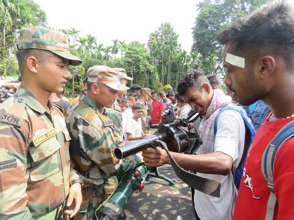 Students getting hands-on experience of handling real weapons during the event in Hashimara. Photo/ANI