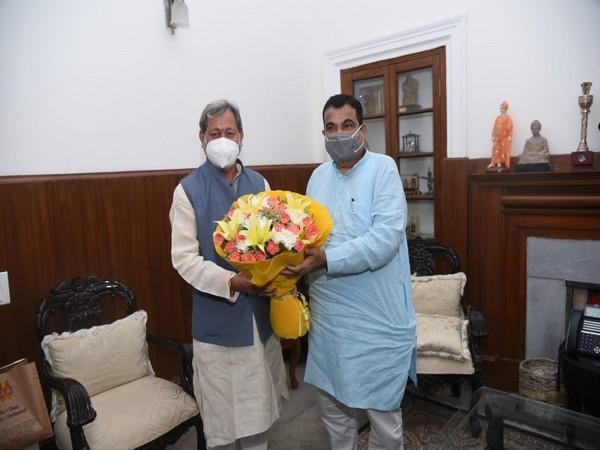 Uttarakhand Chief Minister Tirath Singh Rawat greeting Union Road Transport Minister Nitin Gadkar. i