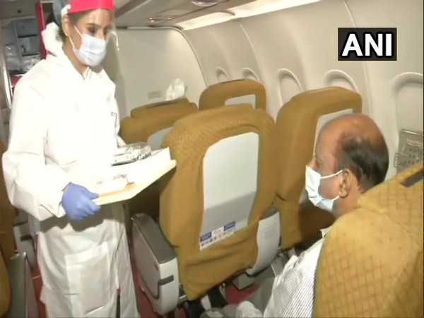 Air hostess serving food to a passenger in Air India flight. (Photo/ANI)