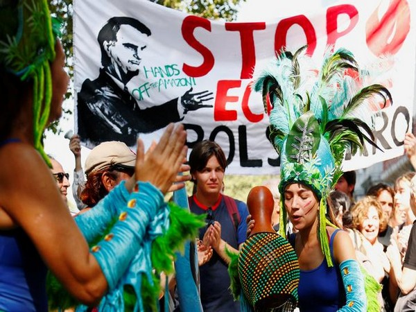 Protesters wearing Brazilian carnival costumes dance during a demonstration to demand protection for the Amazon rainforest outside the embassy of Brazil in Brussels