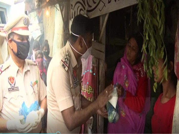 Police officials distributing free food packets to poor in Amritsar on Wednesday. [Photo/ANI]