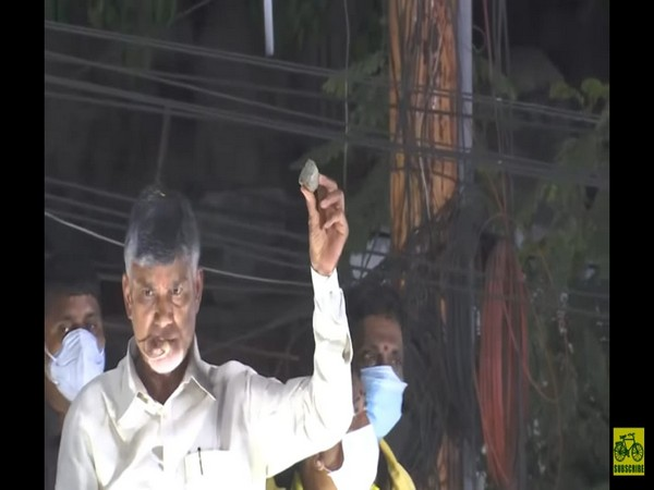 Former Andhra CM showing the stone which was pelted on his convoy. (Photo/ANI)