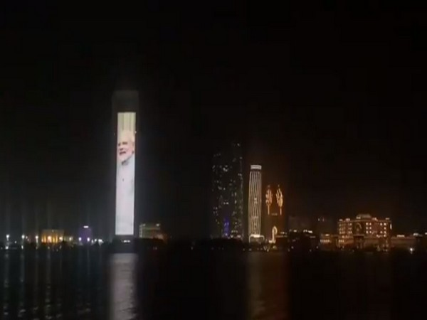 The facade of the ADNOC tower in Abu Dhabi lit up with flags of India and UAE and portraits of two leaders of both countries.