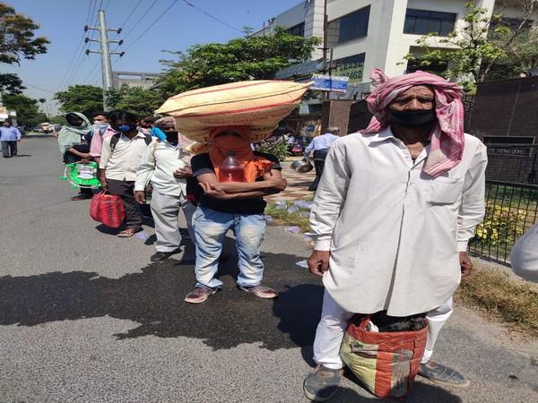 Acchelal, among other migrants queued up at Shaheed Hemu Kalani Sarvodaya Bal Vidyalaya, Lajpat Nagar on Wednesday. Photo/ANI