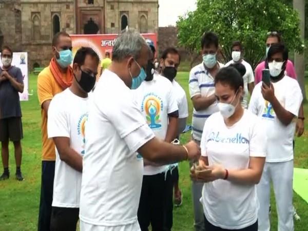 Delhi BJP President Adesh Kumar Gupta distributing masks and sanitisers to people on International Yoga Day in New Delhi on Sunday. [Photo/ANI]