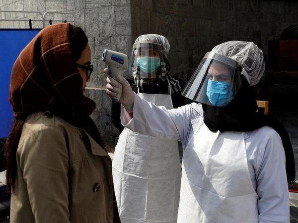 Afghan health worker in protective gear checks the temperature of a woman in Kabul