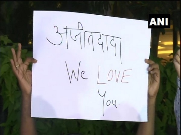 """NCP workers holding pla cards reading """"Ajit Dada, we love you"""" in Mumbai on Tuesday. (Photo/ANI)"""
