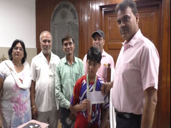 Aligarh District Magistrate Chandrabhushan Singh (right) giving cheque to Chandhary Singh Choudhary.