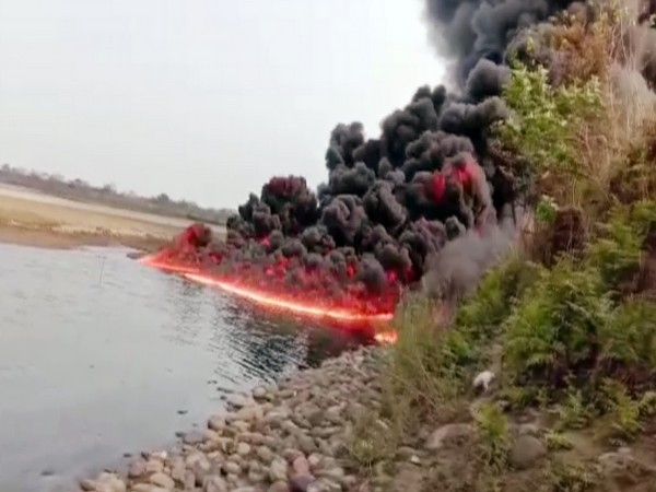 Heavy smoke and flames come out after a blast in oil pipeline, near Burhi Dihing river in Dibrugarh on Monday.