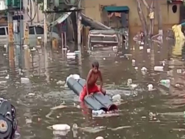 A boy rowing a boat in the stagnane water in Patna on Friday [Photo/ANI]