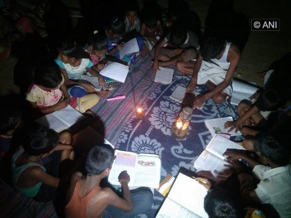 Children studying using a Kerosene lamp in Trishuli village of Balrampur. [Photo/ANI]