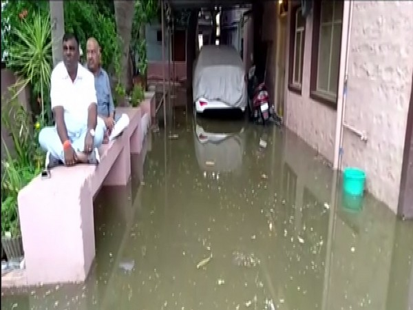 Bellari MLA Somashekhar Reddy staging a sit-in outside his residence agaist overflowing sewage water. Photo/ANI