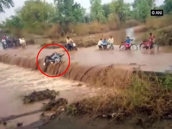 Man riding bike swept away by flood waters in Khargone, Madhya Pradesh on Wednesday. [Photo/ANI]