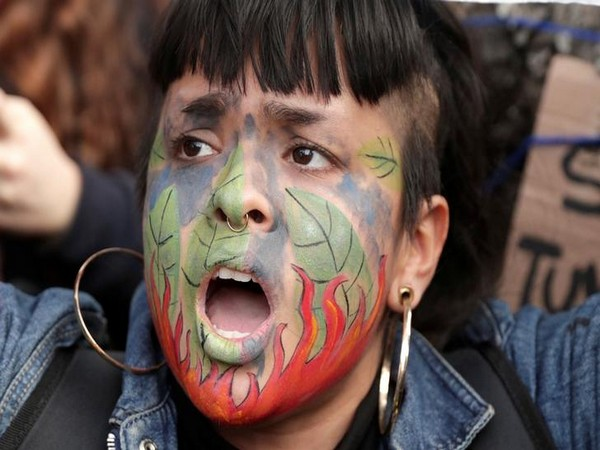 A demonstrator shouts slogans during a protest outside the Brazilian embassy due to the wildfires in the Amazon rainforest, in Lima, Peru