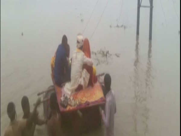 A bride and a groom cross a flooded street in Forbesganj on a makeshift pontoon boat made out of plastic drums.