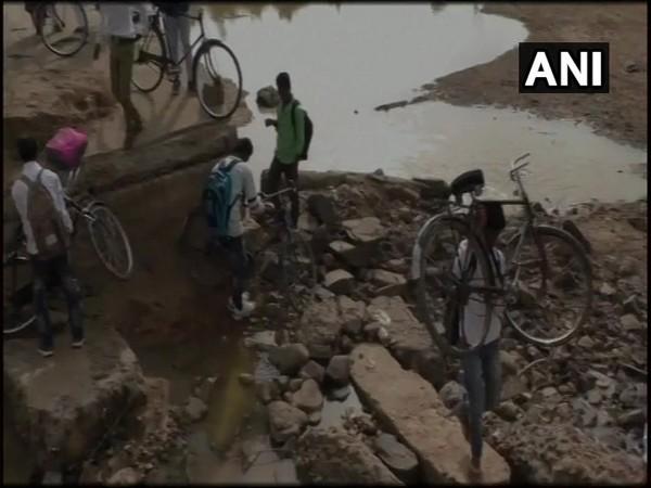 Children crossing the river to reach their school through broken bridge in Umaria