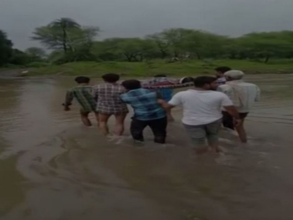 Locals carried a pregnant woman on a cot amid heavy rainfall in Sehore Village, Madhya Pradesh. (Photo/ANI)