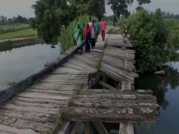 Locals of Majha Kalan and adjacent villages of Basti Division struggle to cross the river via broken bridge. (Photo/ANI)