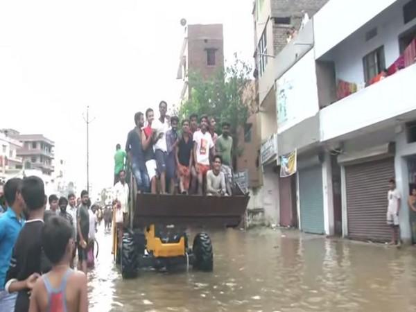 Residents in Patna are forced to commute via Patna Municipality Corporation's JCB. (Photo/ANI)