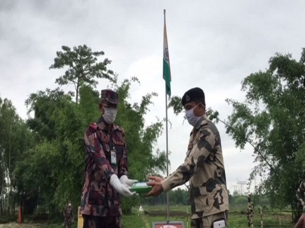 BSF and BGB personnel distribute sweets on the occasion of Eid-ul-Fitr at Fulbari Indo-Bangladesh border on Monday. Photo/ANI