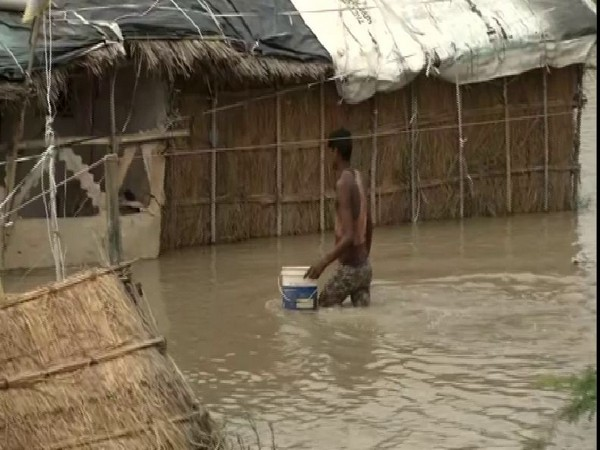 A man trying to cross the flooded road in Yamuna Khadar on Tuesday (Photo/ANI)