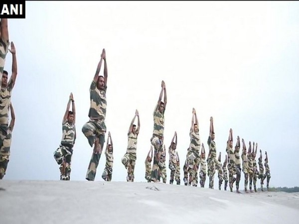 BSF personnel perform yoga asanas on the bank of river Brahmaputra