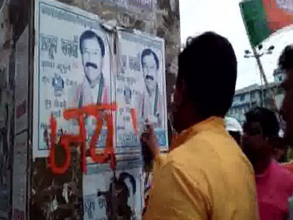 "A BJP worker attempting to write ""Jai Shri Ram"" on TMC MP Prasun Banerjee's posters in Howrah on Sunday. (Photo/ANI)"