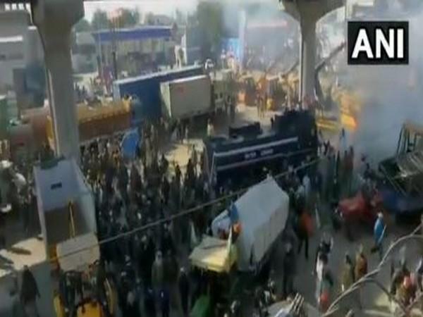 Police use water cannon and tear gas shells to disperse protesting farmers at Tikri border near Delhi-Bahadurgarh highway.