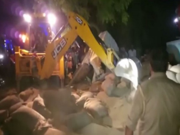 A truck carrying wheat sacks overturned in Badaun district's Alapur area on Monday. Photo/ANI