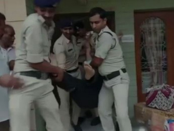 Satyanarayan Rathi being taken out of the house by the police officials. Photo/ANI