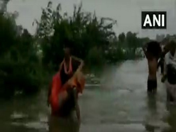 People wade through water in Sheopur, MP