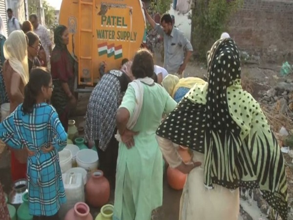 Residents of Mehboob Nagar standing in a queue to fetch water from a water tank. Photo/ANI