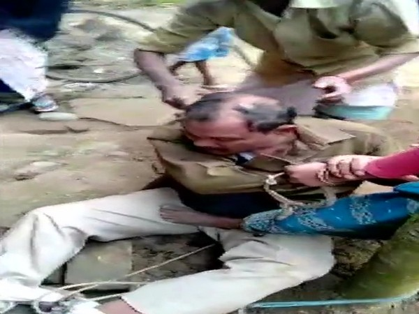 A police officer being tonsured by the mob in Assam's Nagaon (Photo/ANI)