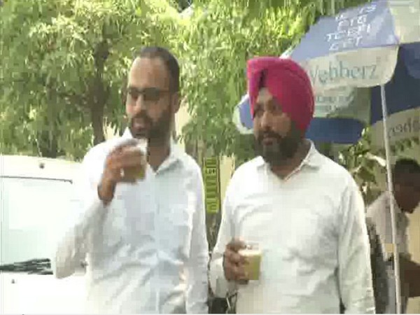 Locals drink sugarcane juice to beat the heat on a hot sunny day in Ludhiana [Photo/ANI]