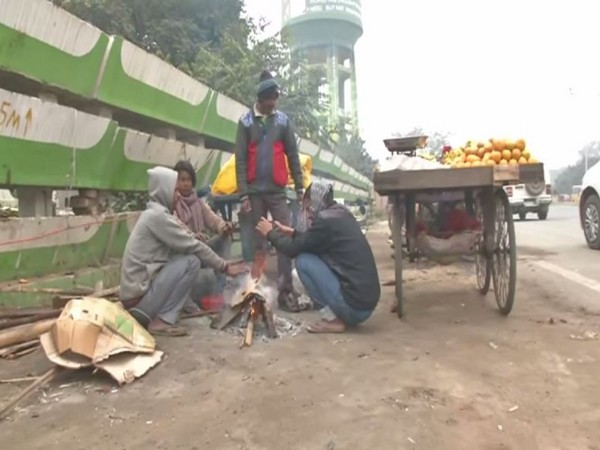 Street vendors sit around a bonfire to keep themselves warm in Patna on Monday (Photo/ANI)