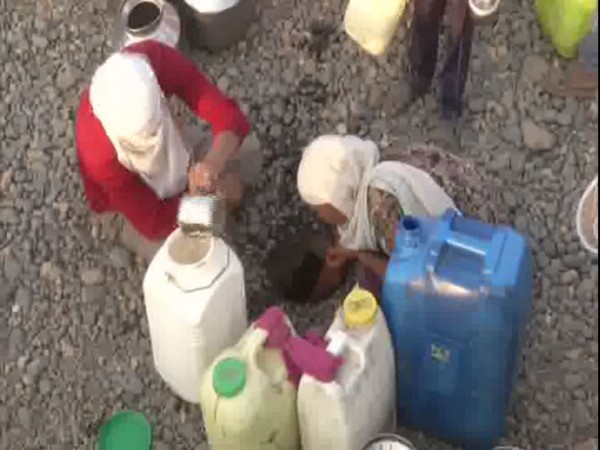 Women pulling water from a small pit in Kawatha village. [Photo/ANI]
